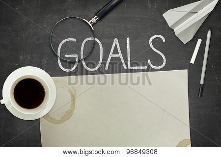 Goals concept on black blackboard with empty paper sheet