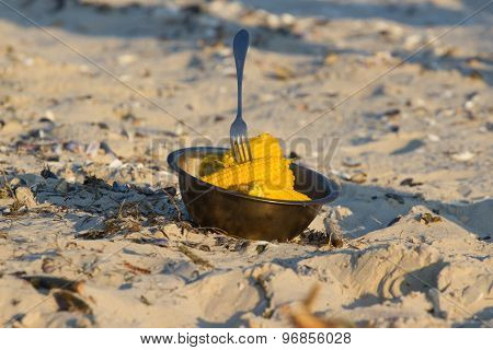 Yellow boiled corn on plate on sand at sunset