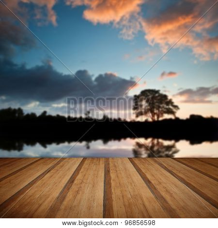 Stunning Sunset Silhouette Reflected In Calm Lake Water With Wooden Planks Floor