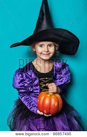 Portrait of little girl in black hat and witch clothing with pumpkin. Halloween. Fairy. Tale. Studio