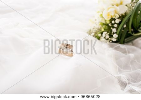 Romance And Wedding Concept. Bride And Groom Wedding Rings On White Dress Material