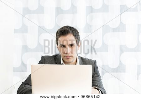 Front View Of A Young Businessman In A High Key Office Typing Information Or Reding A Document On A