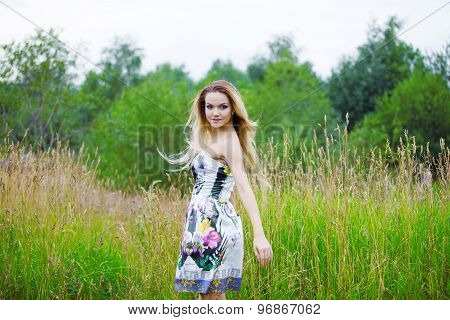 Beauty Girl Outdoors enjoying nature, blond girl in dress  on a meadow