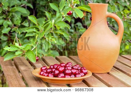 Plate With Cherries And A Jar In The Garden