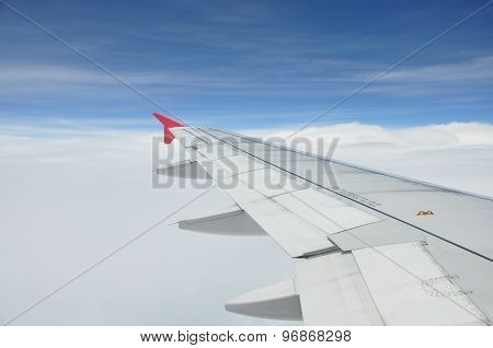 Wing of airplane over the clouds