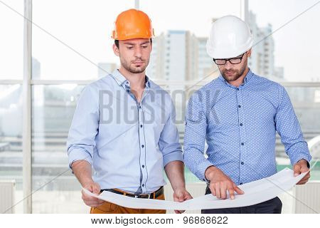 Cheerful young builders are discussing a plan of work