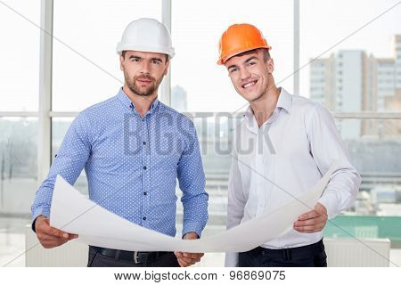 Handsome young builders are discussing a new project