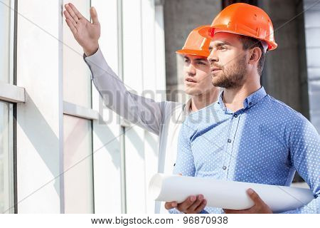 Handsome builders are discussing the plan of work