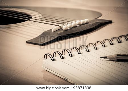 Notebook And Pencil On Guitar Background