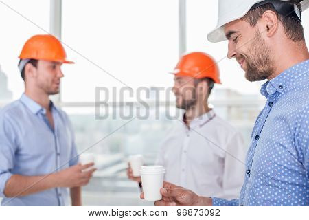 Cheerful young builders are making coffee break