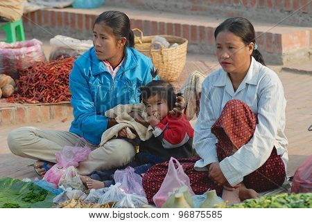 Women with the kid sell vegetables at the food market in Luang Prabang, Laos.