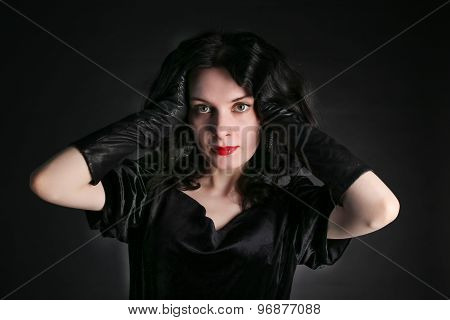 Beautiful trendy girl with fashionable makeup wearing a black dress