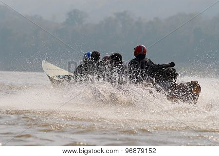 People ride speedboat by Mekong river in Luang Prabang, Laos.