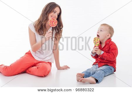 Cheerful young woman is treating her child