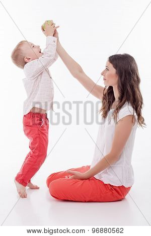 Cheerful young woman is feeding her child