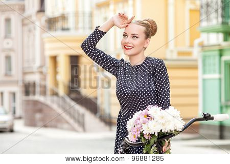 Pretty young woman is walking with a bicycle in city