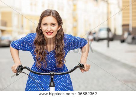 Cheerful young woman is cycling in town