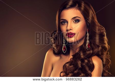Beautiful girl model with long brown curled hair with large earrings with red stone