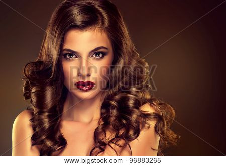 Beautiful girl model with long brown curled hair  and fashion makeup