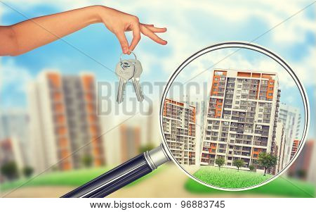 Buildings under loupe and hand with keys