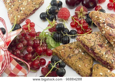 Colorful Red Berry Fruit Falling Out Of Decorated Box And Integral Cookies On White