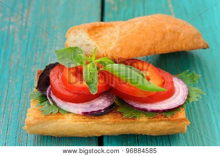 Sandwich With Red Onion, Tomatoes And Basil On Blue Wooden Table