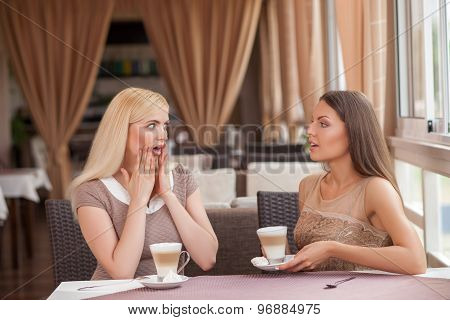 Pretty young girls are gossiping in cafeteria