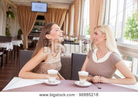 Cheerful young woman are talking in restaurant