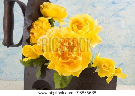 Yellow Roses Bouquet In A Vintage Iron As Vase Against Blue Background