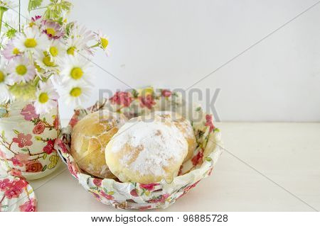 Doughnuts Sprinkled With Powdered Sugar In A Decoupage Decorated Bowl With Flowers On The Table