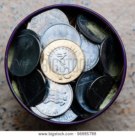 Savings ~ Indian currency coins stored in a tin box kept on a plain background