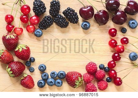 Frame from fresh berries laid around on the wooden plate