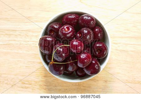 Red sweet cherries with water drops in the ceramic bowl on the wooden plate