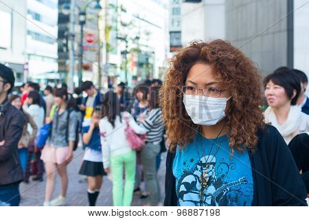 Asian woman is wearing white protective mask in the crowd of people. Tokyo