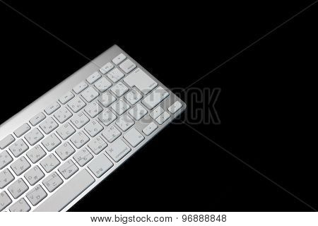 Close-up Of Multilingual  Wireless Keyboard Isolated On Black Background