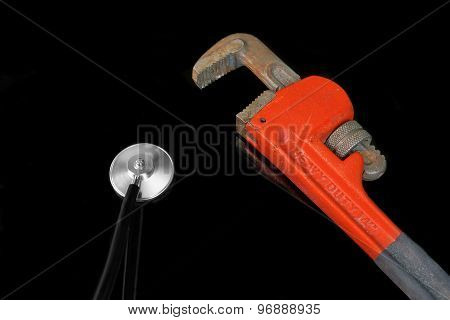 Stethoscope Head And Large Adjustable Wrench On The  Black Background