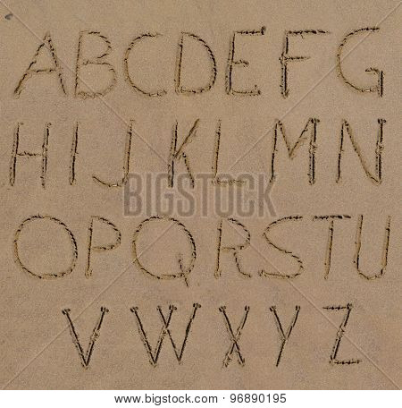 Sand alphabet letters handwritten on beach