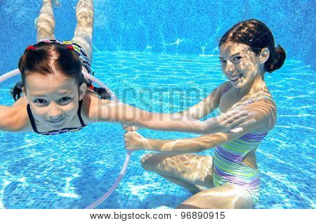 Children swim in pool underwater, happy active girls have fun in water, kids sport
