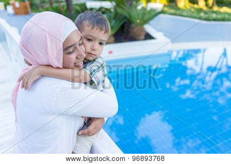 Happy Arabic mother hugging little boy