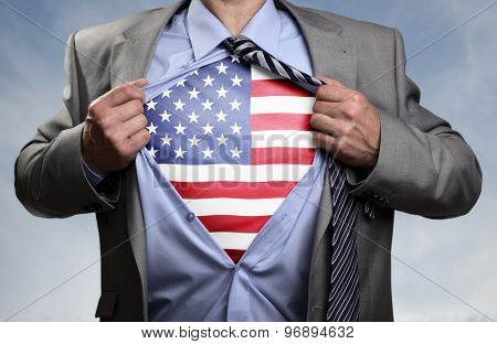 Businessman in classic superhero pose tearing his shirt open to reveal t shirt with the American flag concept for patriotism, freedom and national pride