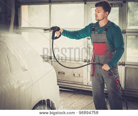 Man worker washing luxury car on a car wash