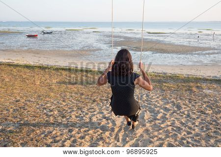 Back View Of A Woman  On A Swing On A Beach  Watching Ocean
