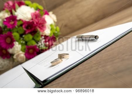 Wedding Register With Pen, Bride And Groom Rings And Bouquet Of Fresh Beautiful Flowers