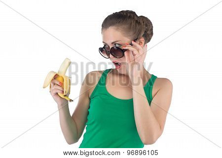 Portrait of surprised woman with banana and sunglasses