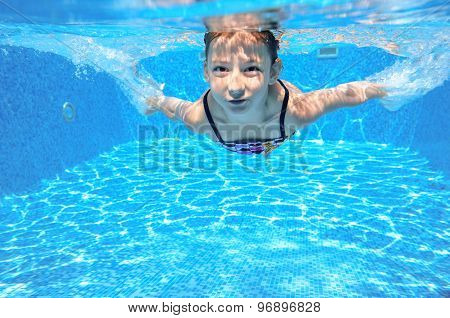 Child swims in pool underwater, happy active girl has fun in water, kid sport on family vacation