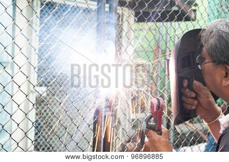 Worker with protective mask welding on metal net