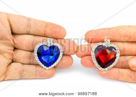 Two Jewelry Hearts On Hand Of Man And Woman