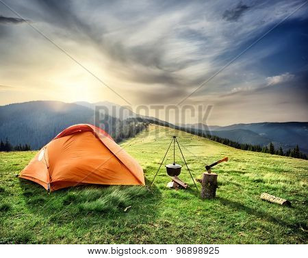 Tent on the hill beneath the mountains