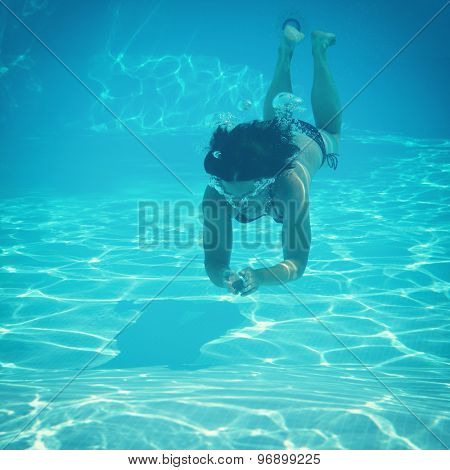 woman swimming underwater in pool, image toned