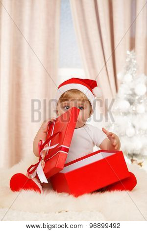 Baby Santa Holds A Big Red Gift Box